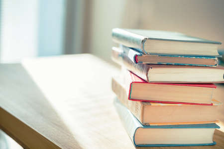 Books on the table in front of sunlight. Shallow depth of field.