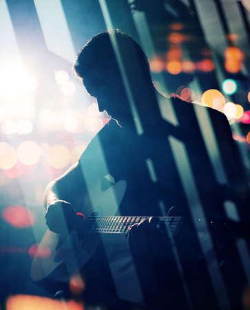 guitarra: El guitarrista tocando la guitarra acústica. Rendimiento Unplugged en la oscuridad. Técnica de doble exposición de ocasión.