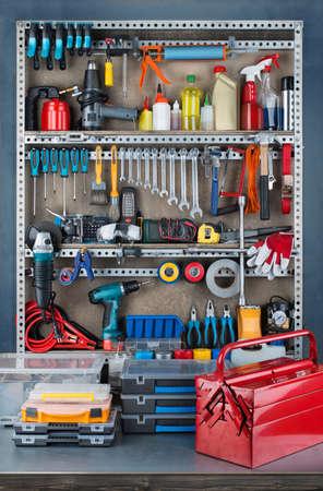 Garage râtelier à outils avec divers outils et de fournitures de réparation à bord et les étagères.