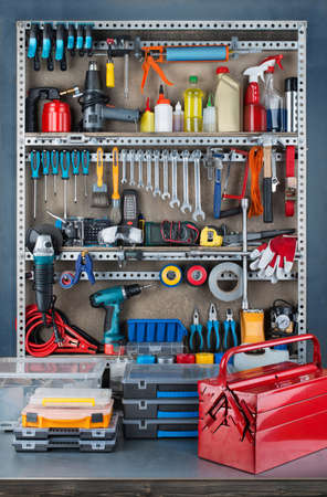 Garage tool rack with various tools and repair supplies on board and shelves. Фото со стока