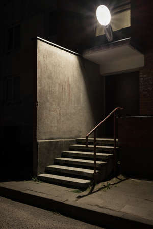 Urban background. Wall and stairs under the lamp light at night.
