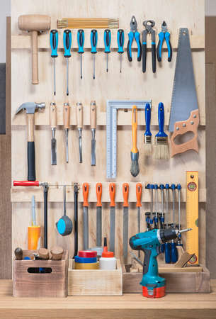 garage background: Garage tool rack with various tools and repair supplies on board .