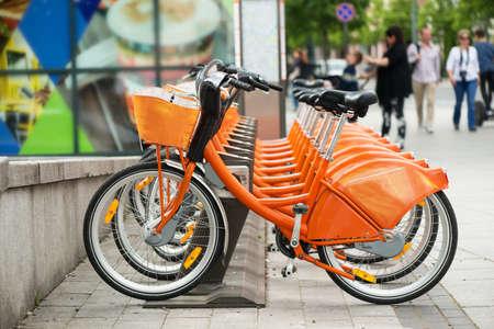 Oranje stad fietsen te huur Stockfoto
