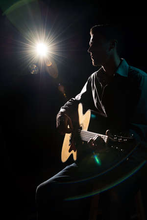 Gitarrist spielt akustische Gitarre. Steckt Leistung im Dunkeln.