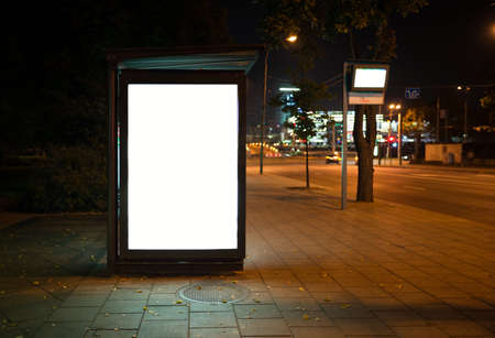 commercial sign: Blank bus stop advertising billboard in the city at night. Stock Photo