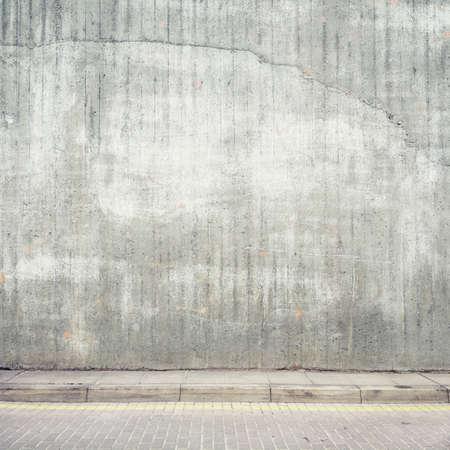 Urban background. Grunge obsolete concrete wall and pavement. Standard-Bild