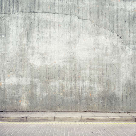 Urban background. Grunge obsolete concrete wall and pavement. Stock Photo