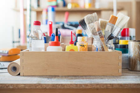 wood craft: Paint brushes and crafting supplies on the table in a workshop.