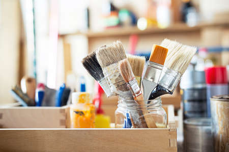 Paint brushes and crafting supplies on the table in a workshop.