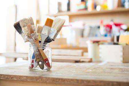 herramientas de carpinteria: Cepillos de pintura sobre la mesa en un taller.