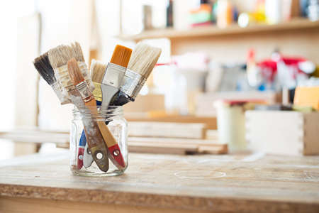 carpentry: Paint brushes on the table in a workshop.