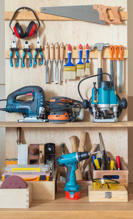 Workshop tool board with various hand tools for repairing and woodworking.