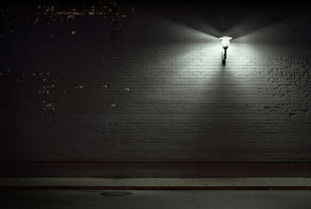 empty street: Urban background. Brick wall under the lamp light at night.