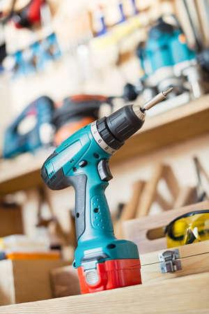 taladro: taladro inalámbrico sobre la mesa en un taller de carpintería o en el garaje. Foto de archivo