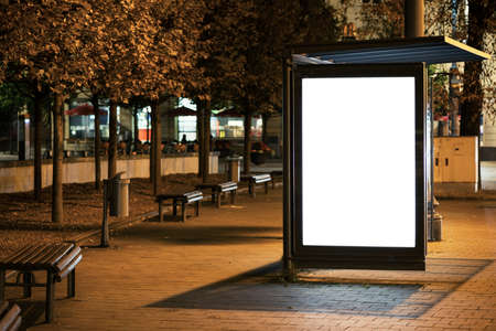 a sign: Blank bus stop advertising billboard in the city at night. Stock Photo