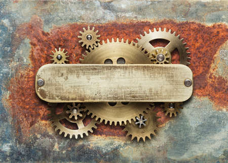 cog: Clockwork mechanism on rusty background made of metal gears and brass plate. Stock Photo
