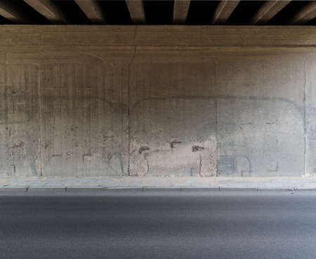 Concrete wall and asphalt road under the bridge. Stock Photo