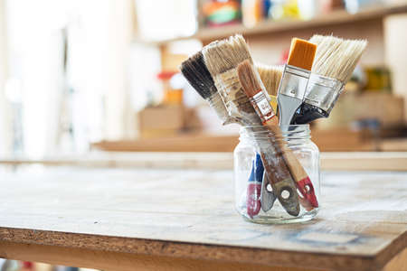 paint box: Paint brushes on the table in a workshop.