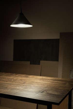 Lamp hanging over empty wooden table in workshop Standard-Bild