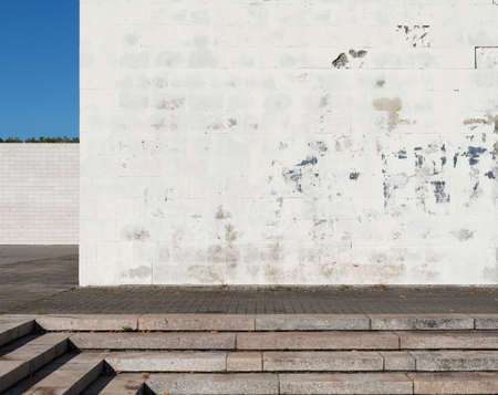 obsolete: Urban background. Grunge obsolete white street wall and pavement.