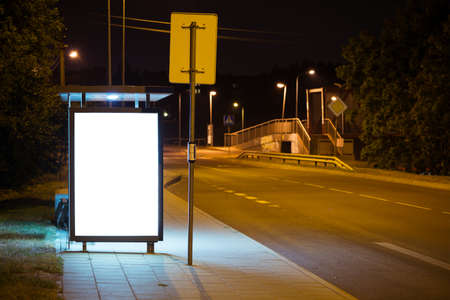 advertising sign: Blank bus stop advertising billboard in the city at night. Stock Photo