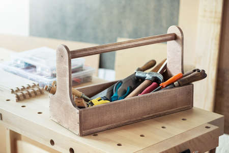 manuals: Wooden toolbox with tools on workbench Stock Photo
