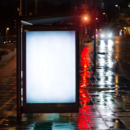 advertising board: Blank bus stop advertising billboard in the city at night. Stock Photo