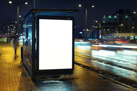 Blank bus stop advertising billboard in the city at night. Фото со стока