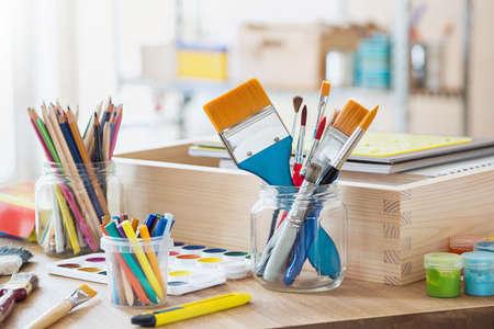 Cepillos de pintura y materiales de artesanía en la mesa en un taller.
