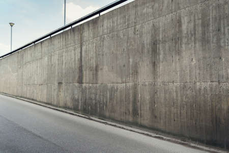 Urban background. Empty concrete wall and asphalt road.