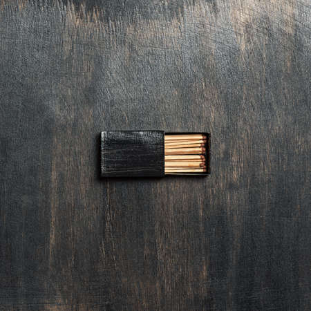 Open black matchbox on the table.