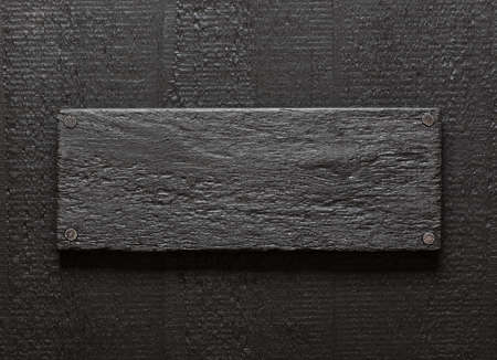 Dark painted rough lumber board nailed to black wood background