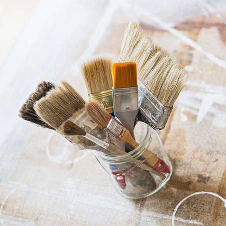 Paint brushes on the workshop table. Stock Photo
