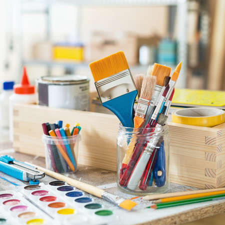 Paint brushes and crafting supplies on the table in a workshop. 版權商用圖片 - 93609171