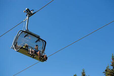 Selva Gardena -Trentino Alto adige - 07/19/2016 People sitting on the chairlift during a summer hike in the mountains