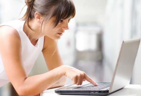 businesswoman at laptop against interiors background photo