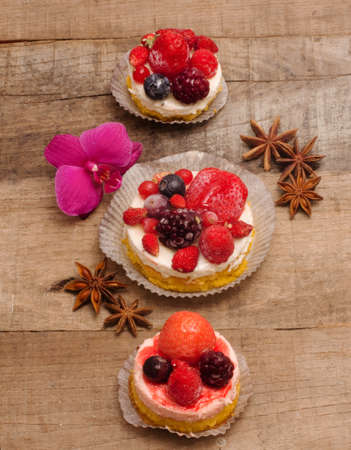 berries cupcakes over wood table photo