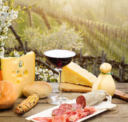ham and cheese:  red wine glass with cheese anf ham against vineyards hill