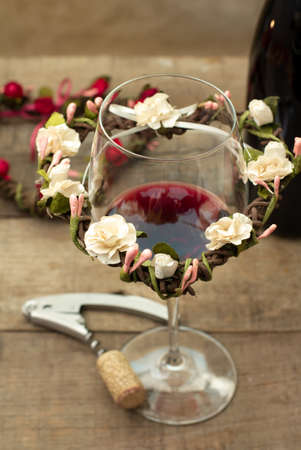red wine glass with corkscrew and floral decoration photo