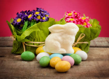 white chocolate bunny and easter eggs  against pink background photo