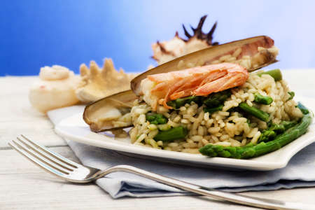 delicious risotto light  with asparagus, razor shell and prawn photo