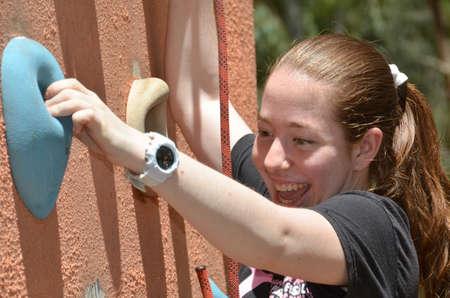 climbing  wall: Young woman having fun on an outdoor climbing wall