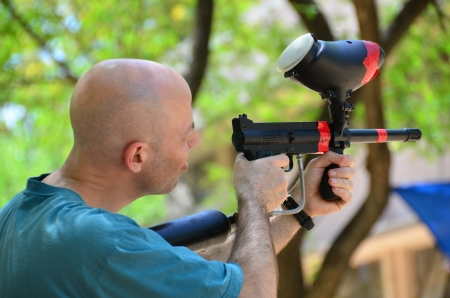 A man target practicing with a paintball gun   holding a paintball rifle photo