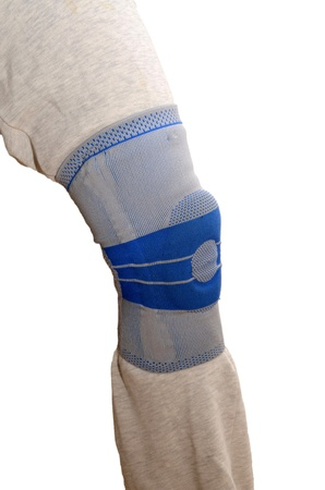 kneecap: Sports knee brace - a stabilizing silicone blue and gray medical sports knee brace worn over sweatpants Stock Photo