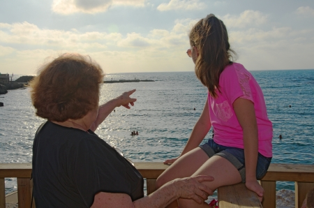 Grandmother and granddaughter admiring the view at the historic Caesarea Harbor of the Mediterranean photo