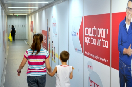 Two kids aged 12 and 6 boarding the airplane with Hebrew advertisements in the background at Tel Aviv Airport   TLV or Ben Gurion Airport  on August 18, 2013 in Tel Aviv, Israel