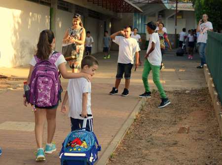 KFAR SABA, ISRAEL - AUGUST 27  Back to school  an 11-year-old girl accompanying her first-grader 6-year-old brother on the first day of school  on August 27, 2013 in Kfar Saba, Israel