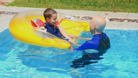 Father and son in a swimming pool - father and son having fun in the swimming pool with a floating cushion  seat photo