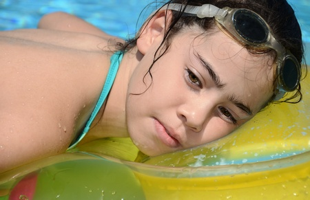 floats: Teenage girl resting in the pool - young woman resting on a floating cusion in the swimming pool Stock Photo