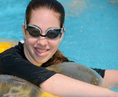 floats: Young woman wearing goggles - teenage girl in a swimming pool on a floating cusion